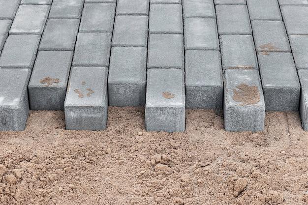 Bestrating reparatie en leggen van bestrating platen op de loopbrug, gestapelde tegelblokjes op de achtergrond. bestrating leggen in de voetgangerszone van de stad, zand opvullen. wegtegels en stoepranden.