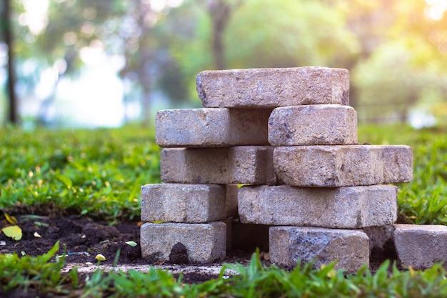 Bestratingsbakstenen en het bedekken plakken op het gras in het gras