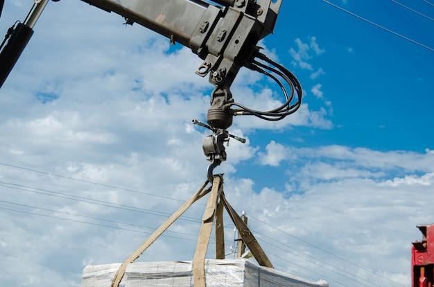 Bestratingsplaten lossen van een vrachtwagen. mannen lossen straatstenen met een manipulator. werknemers lossen bouwmaterialen uit een grote machine.