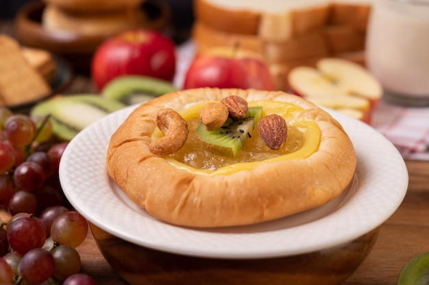 Bestrijk het brood met jam en leg het met kiwi en druiven