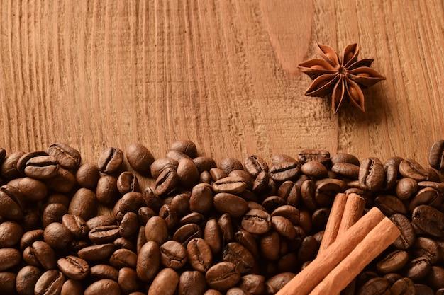 Bestrooide koffiebonen onderaan de foto, evenals anijs en kaneel.