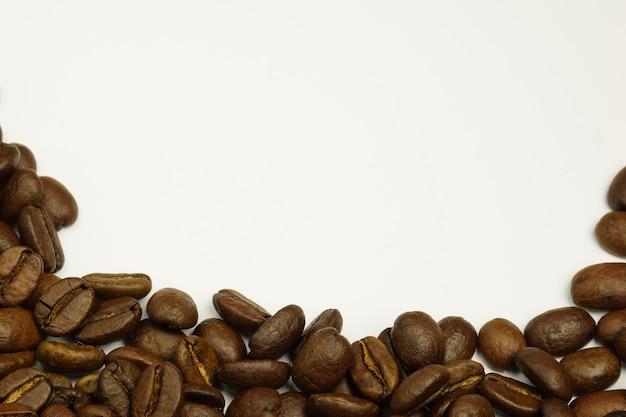 Bestrooide koffiebonen onderaan de foto op een witte achtergrond
