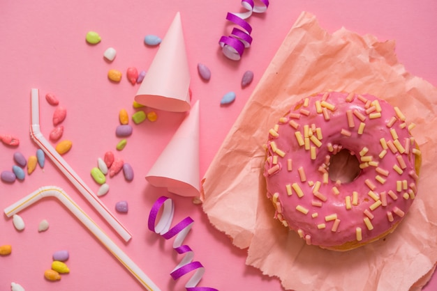 Bestrooide roze doughnut. berijpte bestrooide doughnut op roze achtergrond.