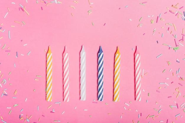 Bestrooit en rij van kaarsen op roze achtergrond