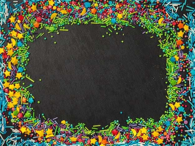 Bestrooit korrelig. zoetwaren concept. zoete confetti op een zwarte achtergrond.