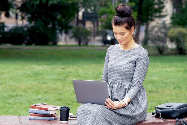 Bestudeert het studenten volwassen meisje door laptop bij park.