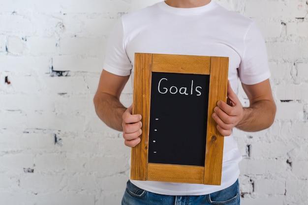 Bestuur met nieuwe doelen. voer nieuwe doelen in. de inscriptie in krijt op een zwart bord in een frame van hout.