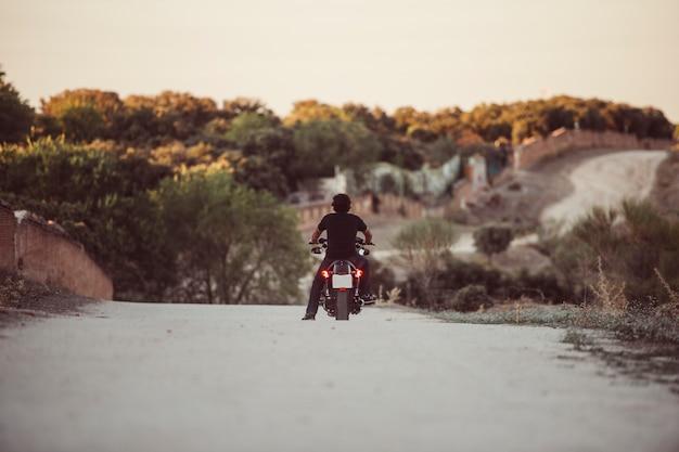 Bestuurder beheert zijn motorfiets bij zonsondergang