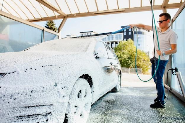 Bestuurder die zijn auto met zeepschuim schoonmaakt