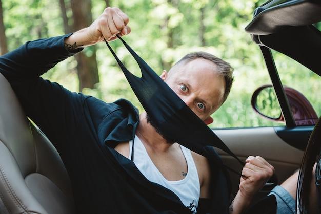 Bestuurder in zwart gezichtsmasker in rode auto open bovenkant op aardachtergrond.