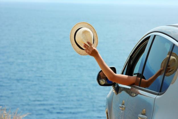 Bestuurder meisje met hoed in auto op zee in de zomer