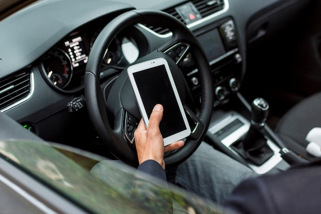 Bestuurder zoekroute met telefoon in auto