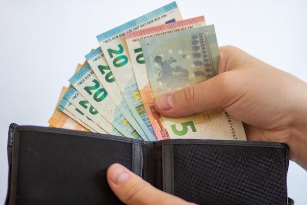 Betaal in euro's haal euro's uit uw portemonnee eurobiljetten op een witte achtergrond met een portemonnee
