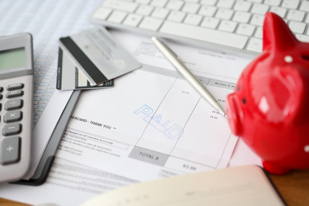 Betaalde woorden en rekenmachine met een spaarvarken bij het tellen van papier voor zakelijke betalingen