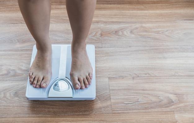 Betaalt van aziatische vrouw op gewichtsschaal, verliest gewichtsconcept