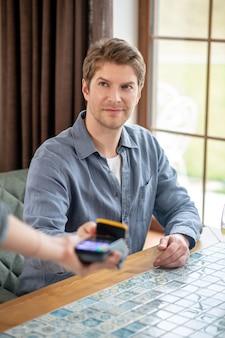Betaling. jonge volwassen glimlachende man die smartphone vasthoudt aan draagbare betaalautomaat om de check-in in restaurant te betalen