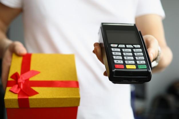 Betaling per creditcard plastic bankkaart bij terminal aan koerier met geschenkdoos