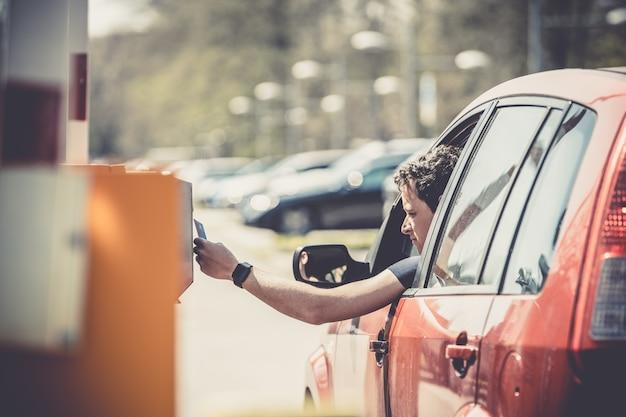 Betaling voor parkeren met creditcard. rode auto