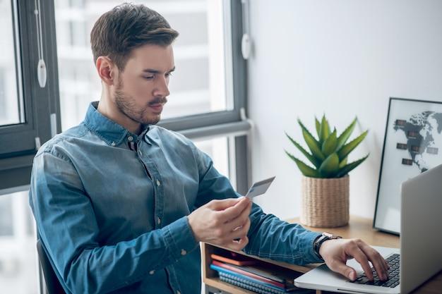 Betalingen online. jonge man in denim overhemd periodieke betalingen online doen