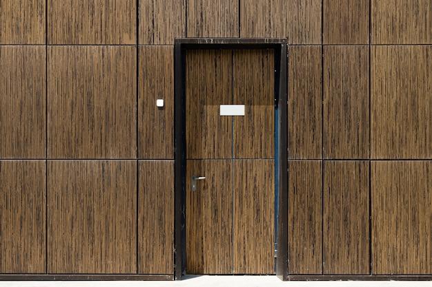 Betegelde bruine muur met ingebouwde gecamoufleerde deur, vooraanzicht. copyspace op deur.