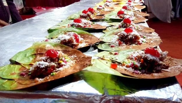 Betelblad of meetha banarasi paan gegarneerd met kersenfruit en allerlei indiase banarasi-ingrediënten of masala te koop.