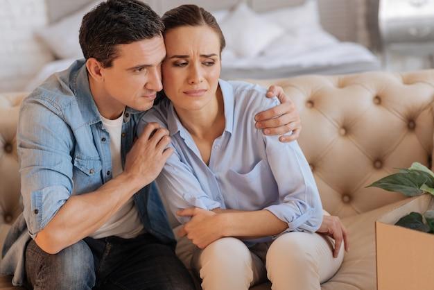 Beter. attente vriendelijke liefdevolle man zittend op de bank en knuffelen zijn verdrietig ongelukkig ontslagen vrouw terwijl hij probeerde haar aan te moedigen