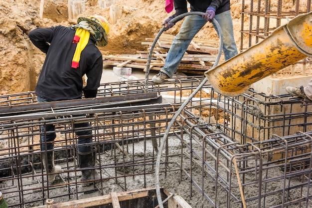 Beton gieten tijdens commerciële betonnen vloeren van gebouwen in de bouwplaats.