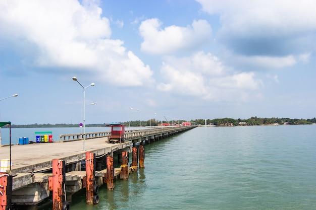 Betonnen brug die zich uitstrekt in de zee onder de heldere hemel en witte wolken