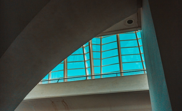 Betonnen gebouw en blauwe hemel gezien door raam