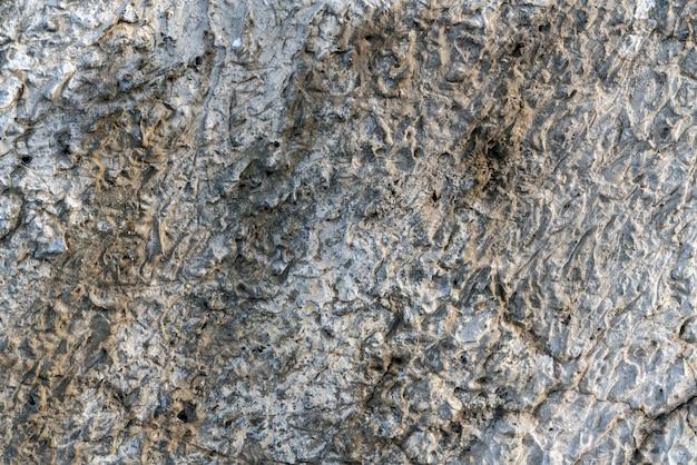 Betonnen getextureerde muur, volume gips, grijze achtergrond