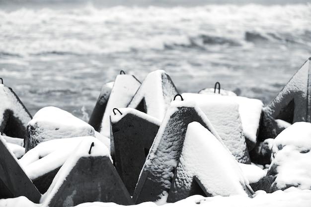 Betonnen golfbrekers bedekt met sneeuw tegen de achtergrond van de winterzee