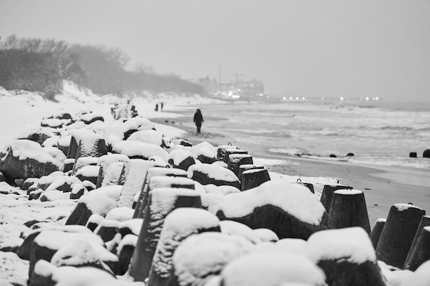 Betonnen golfbrekers bedekt met sneeuw tegen winter zee. kustbescherming in sneeuw