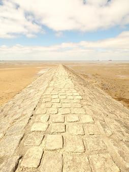 Betonnen loopbrug rond de woestijn onder een hemel vol wolken