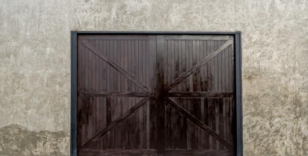 Betonnen muren met grote houten deuren.