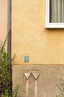 Betonnen muur met raam en struik