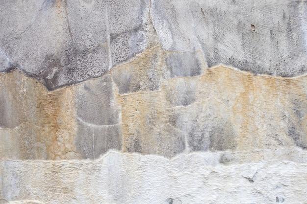 Betonnen muur met scheidingen in de vorm van strepen van geel en wit. interessante achtergrond.