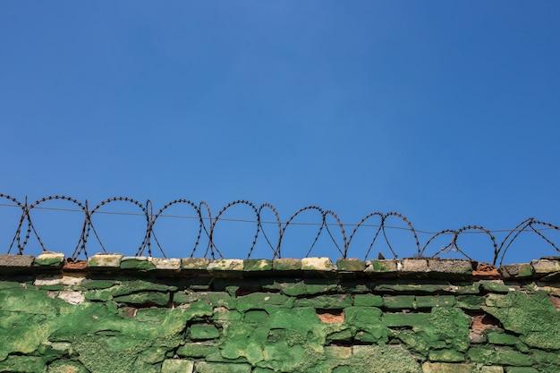 Betonnen muur, tegen de achtergrond van prikkeldraad, het concept van gevangenis, redding