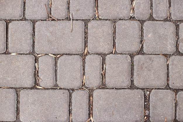 Betonnen of geplaveide grijze bestratingsplaten of stenen voor vloer, muur of pad. traditionele omheining, hof, achtertuin of wegbestrating.