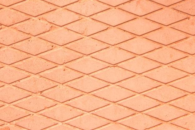 Betonnen plaat. tekening van diamanten. de textuur van de betonnen plaat. grijze achtergrond. roze, oranje achtergrond