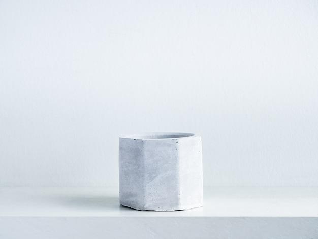 Betonnen pot. lege moderne geometrische cementplanter op witte houten plank op wit