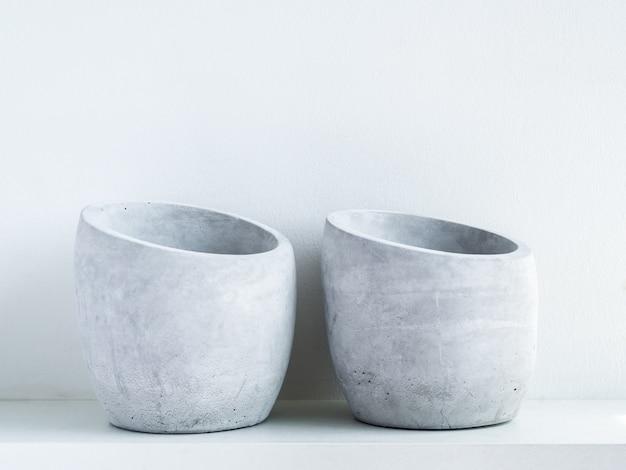 Betonnen pot. twee lege moderne geometrische cementplanters op witte houten plank op wit