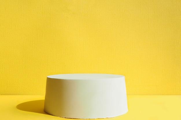 Betonnen voetstuk op een gele achtergrond. staan voor uw product. harde zonschaduwen.