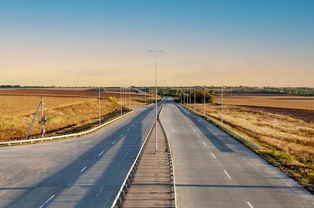 Betonnen weg met tweerichtingsverkeer, scheidingsstrepen, verlichting, gaat in de verte. hogesnelheidsbaan, landbouwvelden aan de zijkanten.