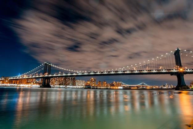 Betoverend beeld van brooklyn bridge en lichten die 's nachts in de vs op het water reflecteren