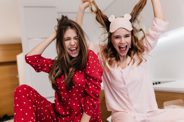 Betoverend donkerharig meisje in rode pyjama poseren met plezier thuis. binnen schot van twee positieve jonge zusters die tijdens fotoshoot lachen.