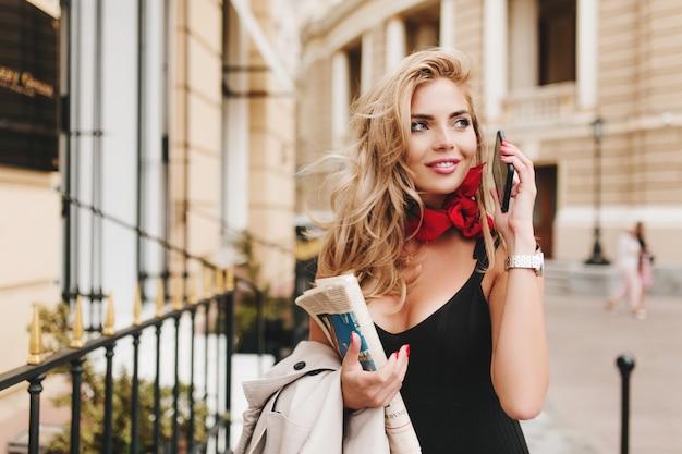 Betoverend gebruind vrouwelijk model dat wegkijkt met een geïnspireerde glimlach die buiten hangt