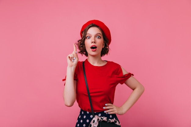 Betoverend kortharig frans model poseren in rode kleding. binnenfoto van geïnteresseerde blanke vrouw in geïsoleerde baret.