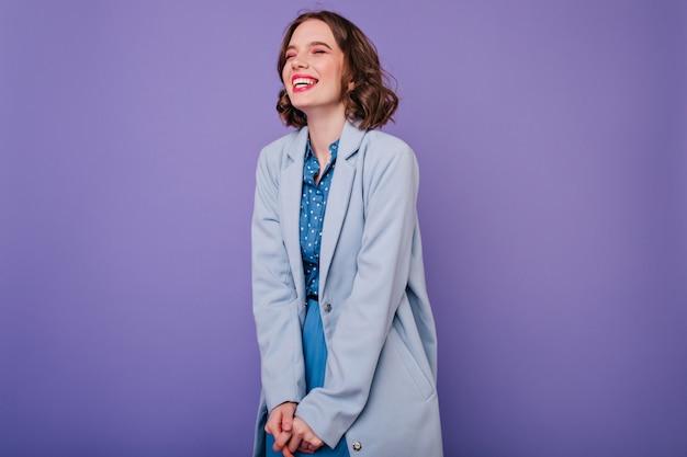 Betoverend krullend meisje dat met gesloten ogen op purpere muur lacht. indoor foto van mooie brunette dame draagt elegante blauwe jas.
