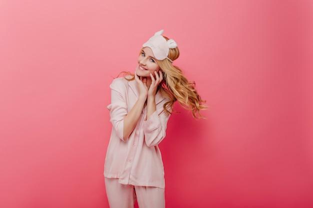 Betoverend krullend meisje die energie in ochtend uitdrukken. aangename blanke vrouw in zijden pyjama poseren op roze muur.