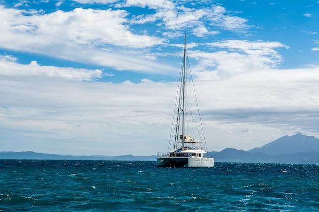 Betoverend landschap van een jacht op de blauwe zee met witte wolken op de achtergrond
